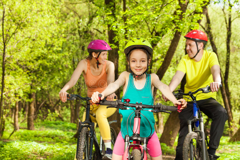 Happy girl having fun the cycling with her parents. Happy teenage girl in helmet having fun the cycling at the spring park with her parents royalty free stock photography