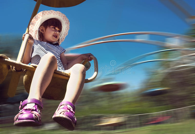 Happy girl having fun on the roundabout stock images