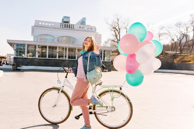 Happy girl with headphones wearing stylish clothes, going to bicycle ride around the city in sunny day. Adorable young royalty free stock photos