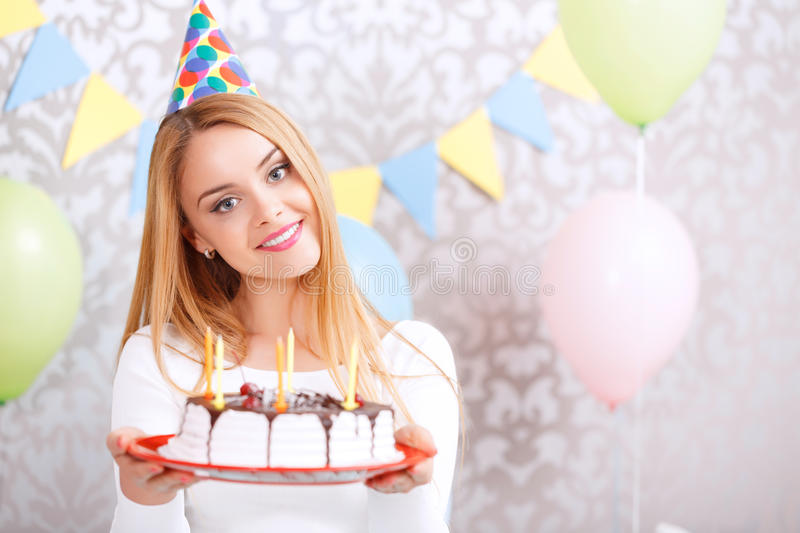 Happy girl and her birthday cake. Portrait of a young beautiful blond girl wearing cone cap holding a red plate with birthday cake with candles in the light stock photo