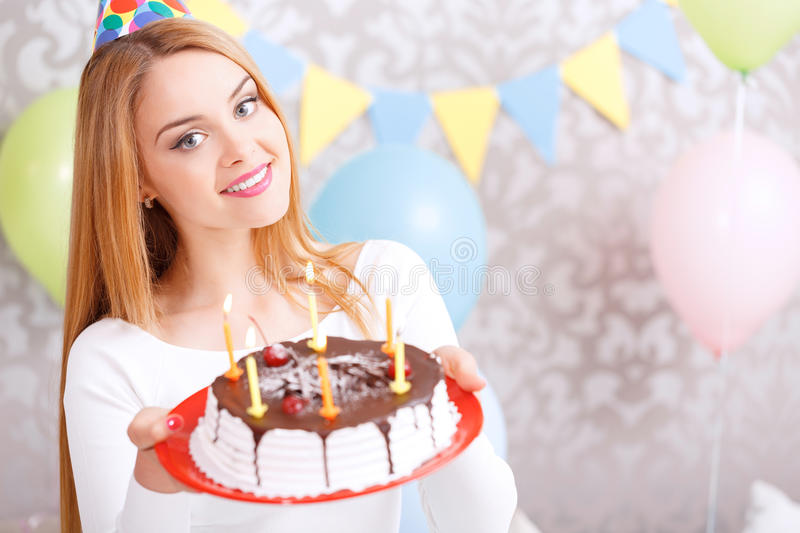 Happy girl and her birthday cake. Portrait of a young beautiful blond girl wearing cone cap holding a red plate with birthday cake with candles in the light stock images