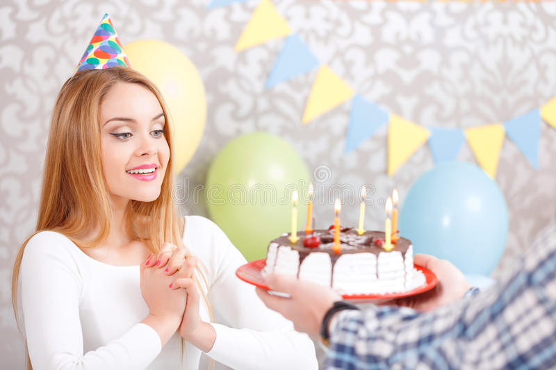 Happy girl and her birthday cake. What a surprise. Young beautiful blond girl wearing cone cap looking surprised when her friend giving her a birthday cake to royalty free stock image