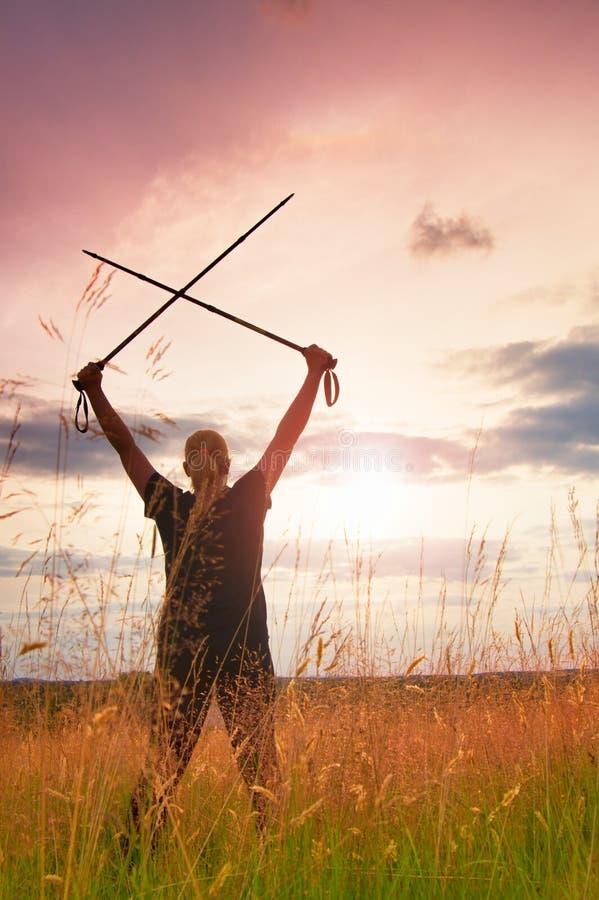 Happy girl hiker with crossed poles in evening golden meadow stock photo