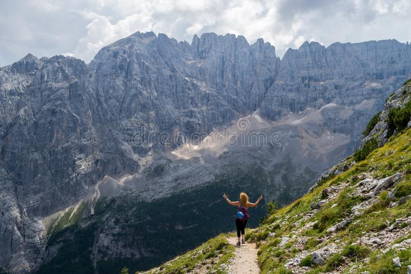 Happy girl hiking and dancing in the Italian Dolomites mountains, with a blue helmet on her backpack royalty free stock photos