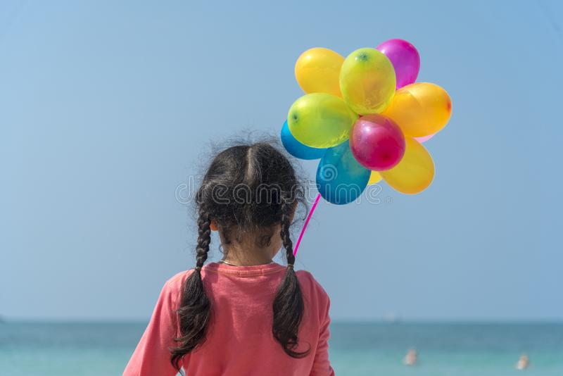 Happy girl holding colorful air balloons on the beach summer times. Happiness playful child joy holiday while travel to summer stock photo