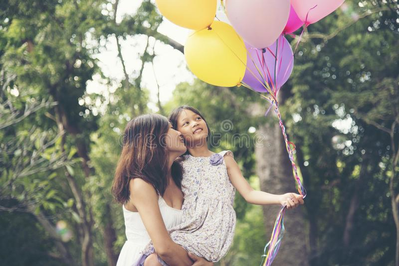 Happy girl holding colorful of air balloons on a green meadow with cloudy and blue sky. Mother hold daughter stock photos