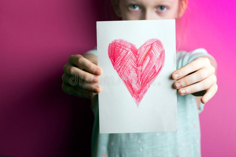 Girl with heart. Happy girl holding drawing with a heart on the valentines day stock photo
