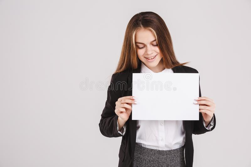Happy girl holding an empty paper sheet suitable for text. Isolated on white background. Copy space stock photography