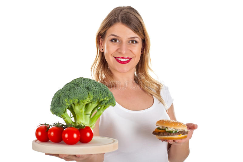 Happy girl holding hamburger & fresh vegetables. Picture of a smiling woman holding a hamburger and fresh vegetables royalty free stock photo