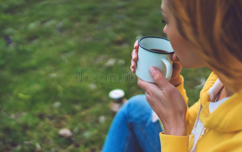Happy girl holding in hands cup of hot tea on green grass in outdoors nature park, beautiful woman hipster enjoy drinking cup stock photography