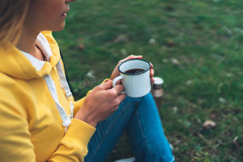 Happy girl holding in hands cup of hot tea on green grass in outdoors nature park top view, beautiful woman hipster enjoy drinking stock photos