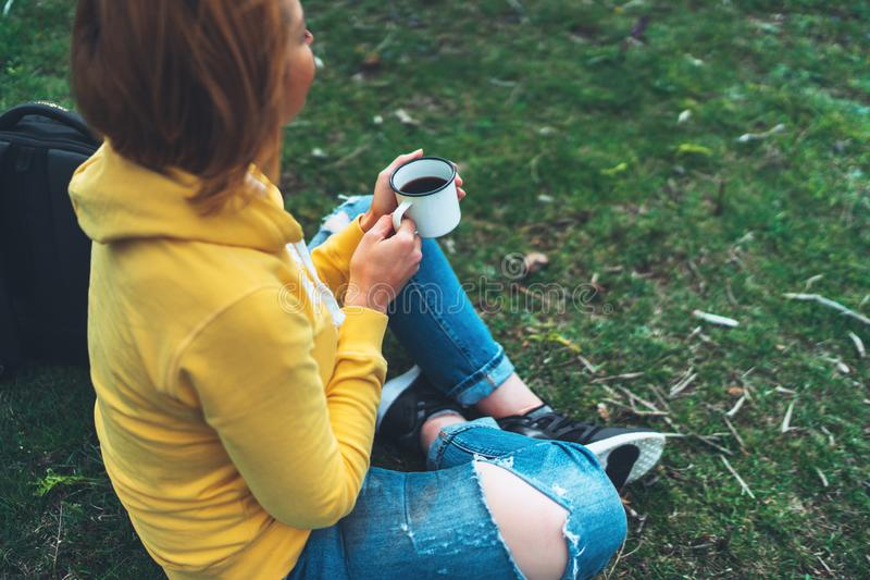 Happy girl holding in hands cup of hot tea on green grass in outdoors nature park top view, beautiful woman hipster enjoy drink royalty free stock photos