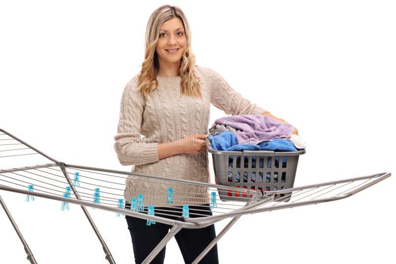 Happy girl holding laundry basket behind clothing rack dryer stock images