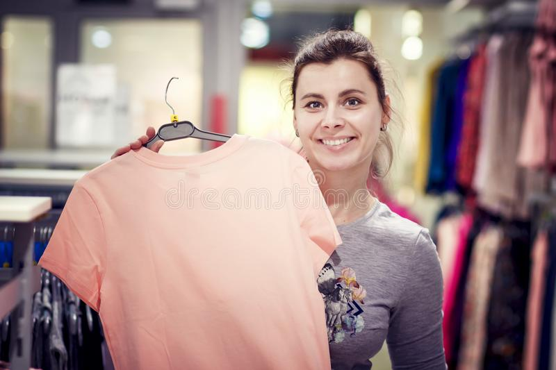 Happy girl is holding a new shirt on hanger in fashion store. Black Friday in fashion boutique. Dressing in the mall stock image