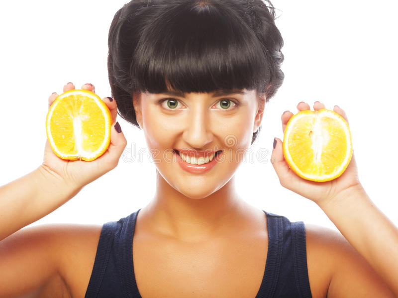 Happy girl holding oranges over face stock photos