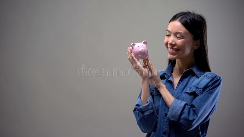 Happy girl holding piggy bank, symbol of thrift, banking services for savings royalty free stock photos