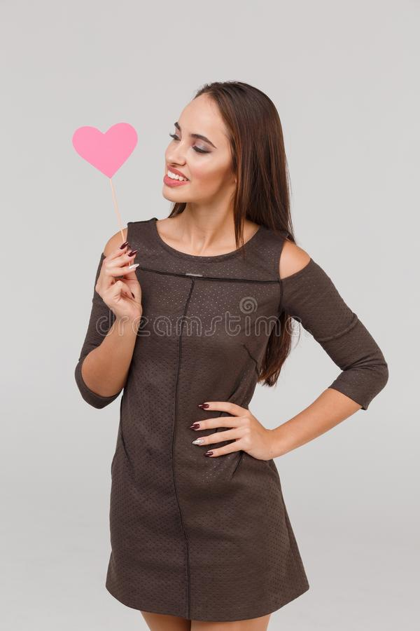 Happy girl is holding a pink heart in her hand on a stick. Isolation. stock photo