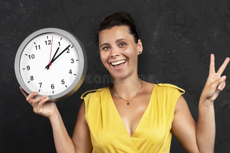 Happy girl holding a round clock in his hand. A young woman keeps track of time. Time concept. stock image