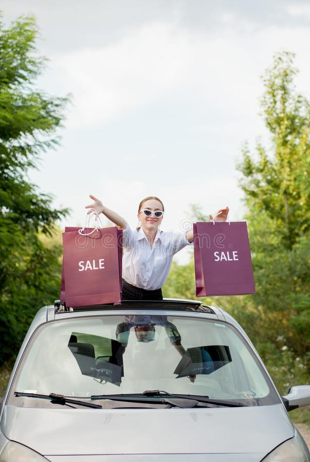 Happy girl holding the shopping packages in the car hatch, concept of discounts and shopping royalty free stock photography