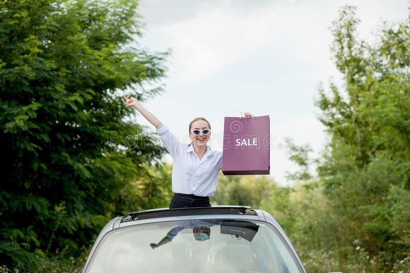 Happy girl holding the shopping packages in the car hatch, concept of discounts and shopping stock photography