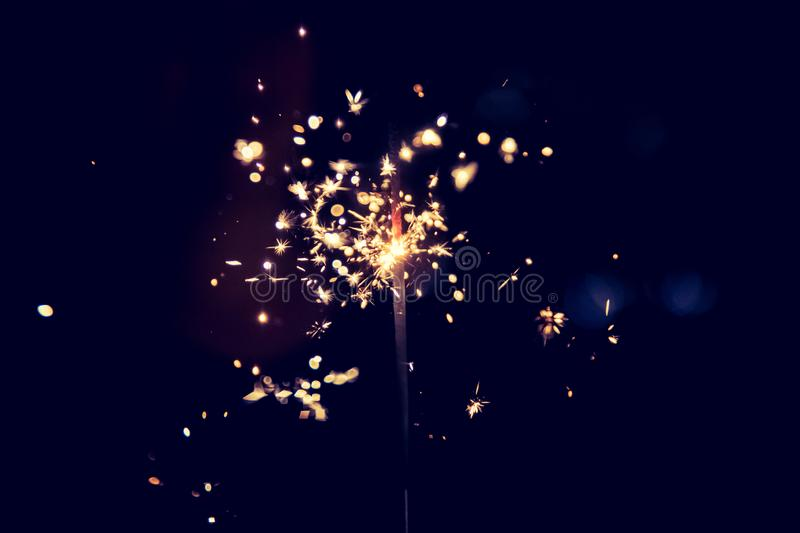 Happy girl is holding a sparkler at Christmas time stock photography