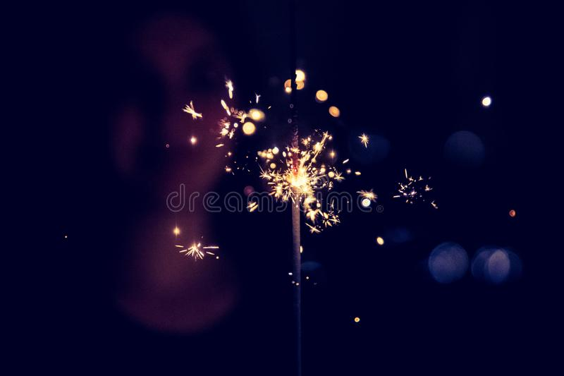 Happy girl is holding a sparkler at Christmas time. Smiling girl is holding a sparkler in her hand, indoor, lights in background, christmas, celebration, happy stock image