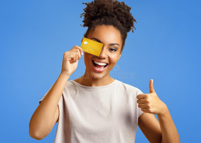 Happy girl holds credit card and shows thumb up. stock photo
