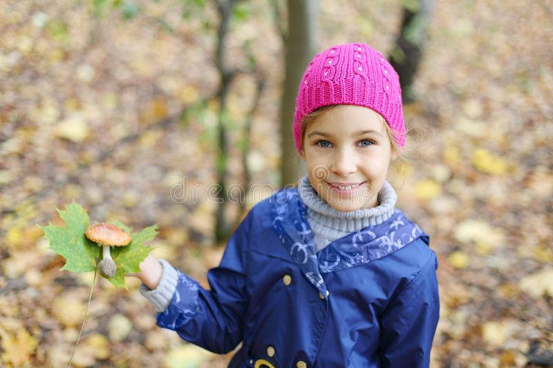 Happy girl holds green leaf. Happy girl in pink hat holds green leaf and toadstool in autumn forest. Shallow depth of field stock images