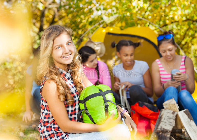 Happy girl holds green sleeping bag during camping royalty free stock photography