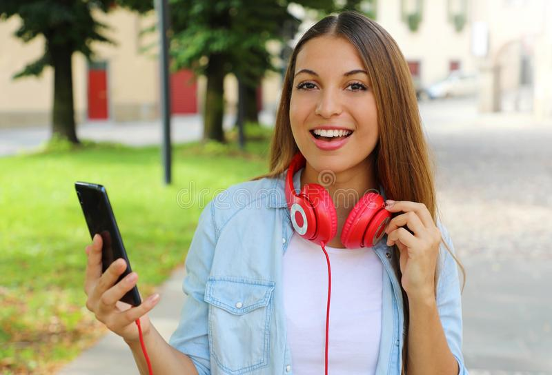 Happy girl holds smart phone for chooses music with her new mobile app outdoors. Looks at camera stock image