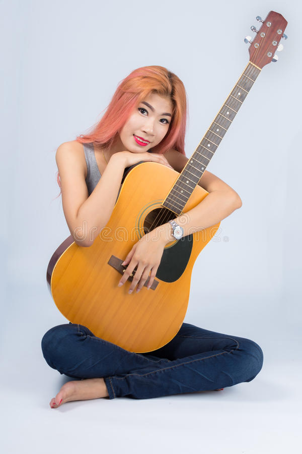 Happy girl hugging a guitar. stock photos