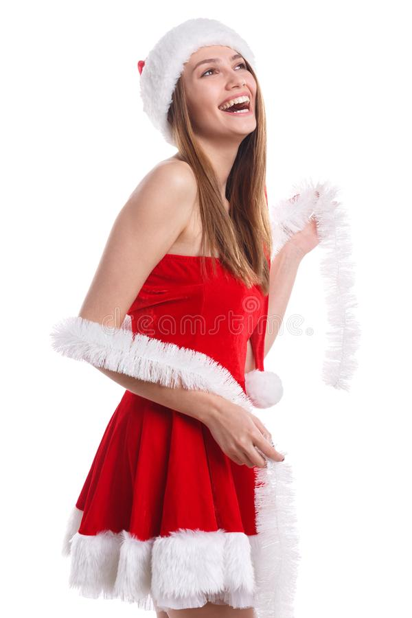 A happy girl im red Christmas costume and white tinsel is laughing happily. Isolated on white background. stock image