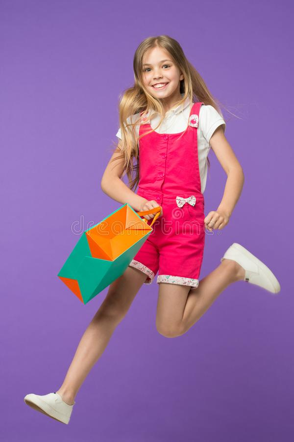 Happy girl jump with shopping bag on violet background. Little child smile with paper bag. Kid shopper in fashion. Jumpsuit. Holiday preparation and celebration royalty free stock image