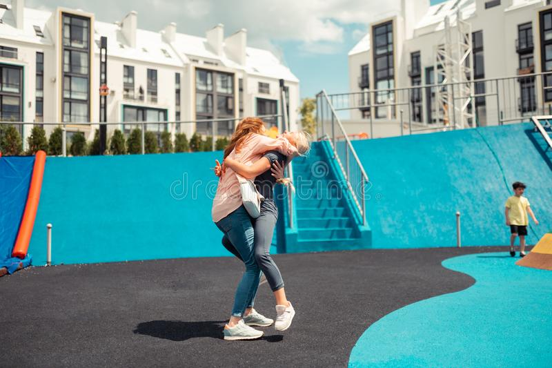 Happy girl jumping on her mum to hug her. Feeling loved. Happy school girl jumping on her mum to hug her after a school day royalty free stock photo