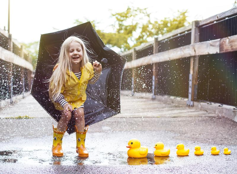 Happy girl jumping. Joyful girl jumping on puddle with ducks next to it royalty free stock images