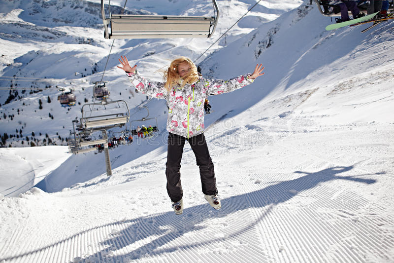 Happy girl jumping on mountains ski slope royalty free stock photography