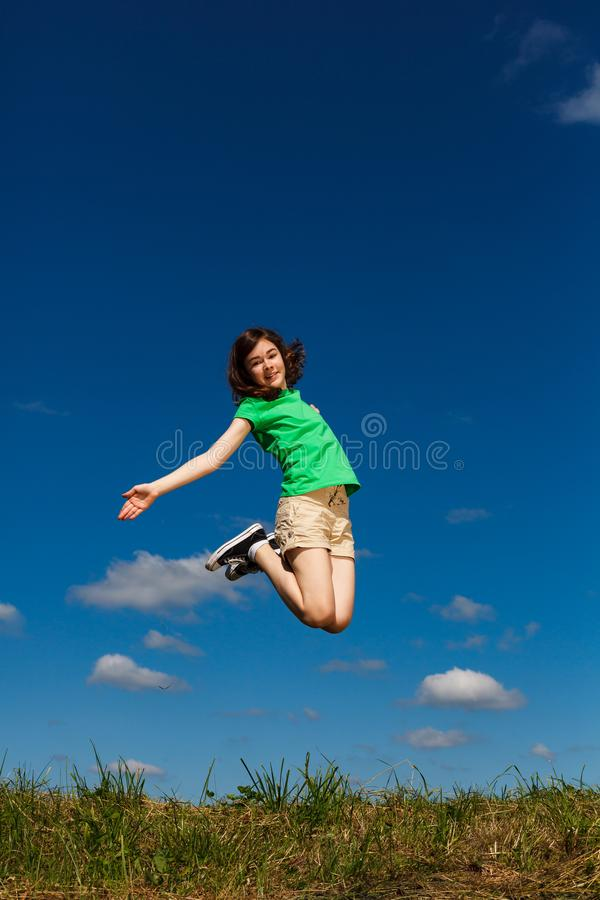 Girl jumping, running against blue sky. Happy girl jumping, running against blue sky royalty free stock images