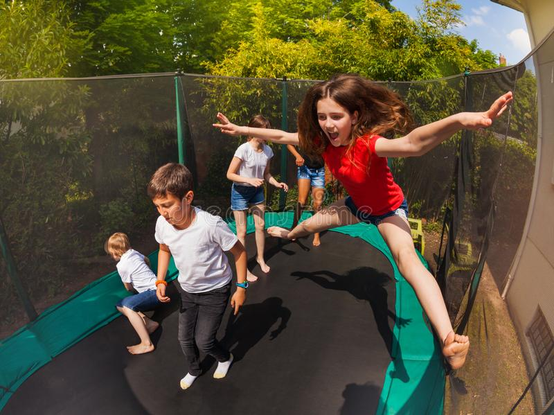 Happy girl jumping on trampoline with her friends stock images