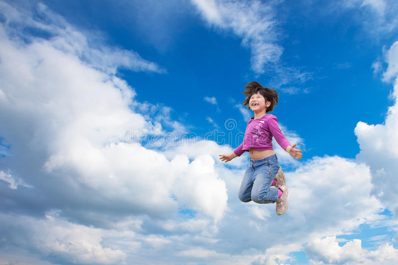 Happy girl jumps into the sky stock photo