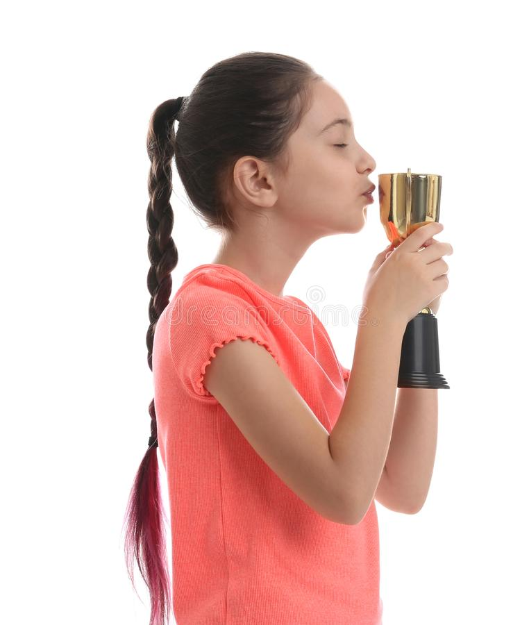 Happy girl kissing golden winning cup isolated on. White stock photography