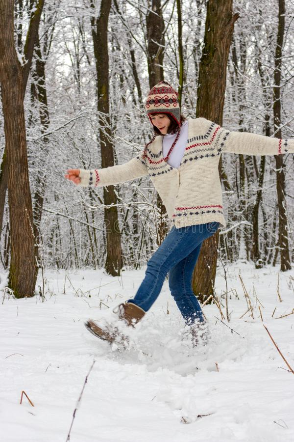 Happy girl in knitted sweater and hat playing with snow in winter forest. Christmas and winter holidays background. Winter activity. Joyful vacation. Happiness stock images