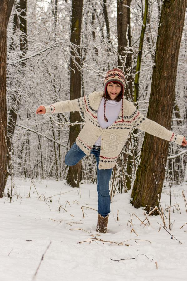 Happy girl in knitted sweater and hat playing with snow in winter forest. Christmas and winter holidays background. Winter activity. Joyful vacation. Happiness royalty free stock photography