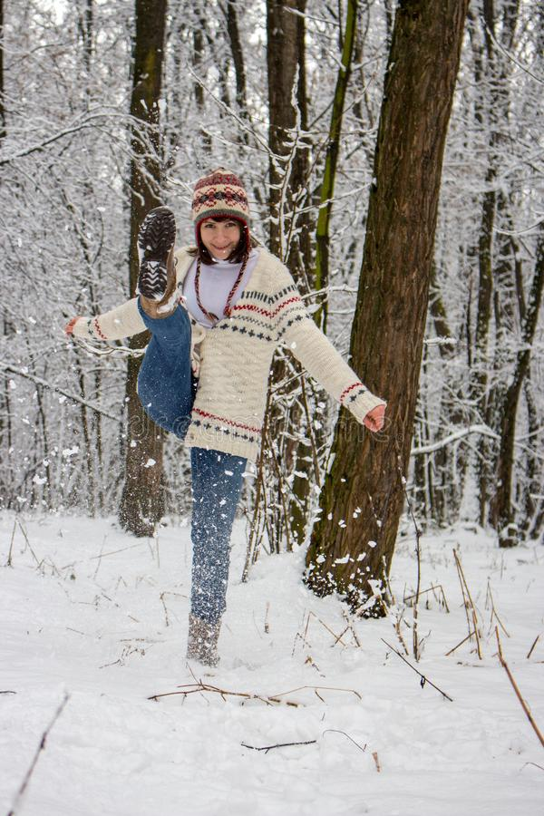 Happy girl in knitted sweater and hat playing with snow in winter forest. Christmas and winter holidays background. Winter activity. Joyful vacation. Happiness stock photos