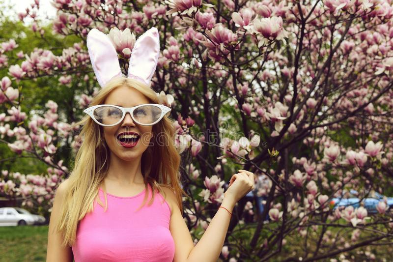 Happy girl laughing at blossoming tree with magnolia flowers. Happy girl or cute woman with bunny ears and funny glasses with long, blond hair laughing in pink stock photography