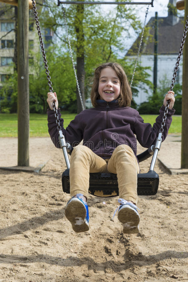 Happy girl laughing and swinging on a swing royalty free stock images