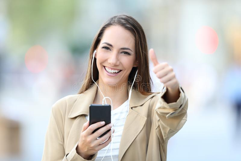 Happy girl listening to music posing with thumbs up royalty free stock photo