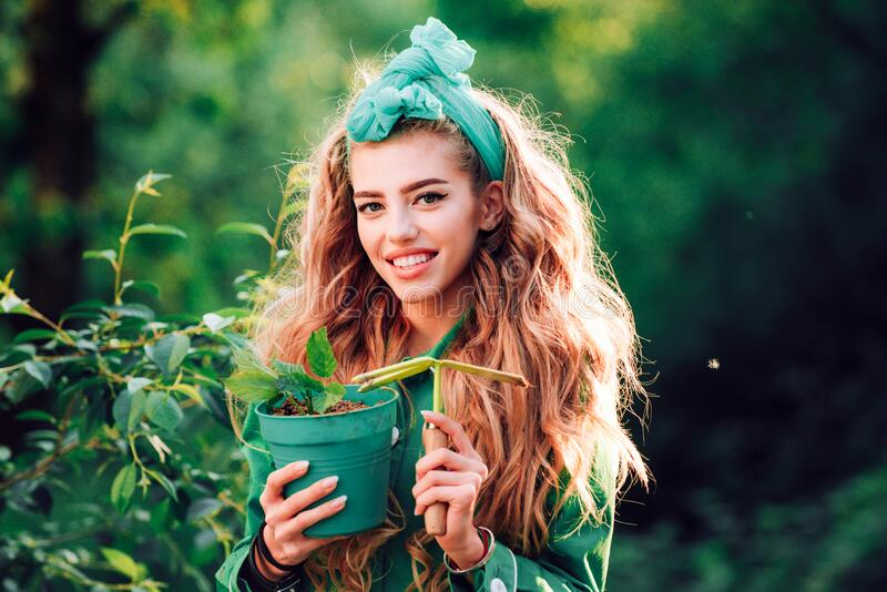 Happy girl with long hair holding a flower pot. Planting and flower growing concept. Beautiful girl in spring garden. Happy girl with long hair holding a flower royalty free stock photo