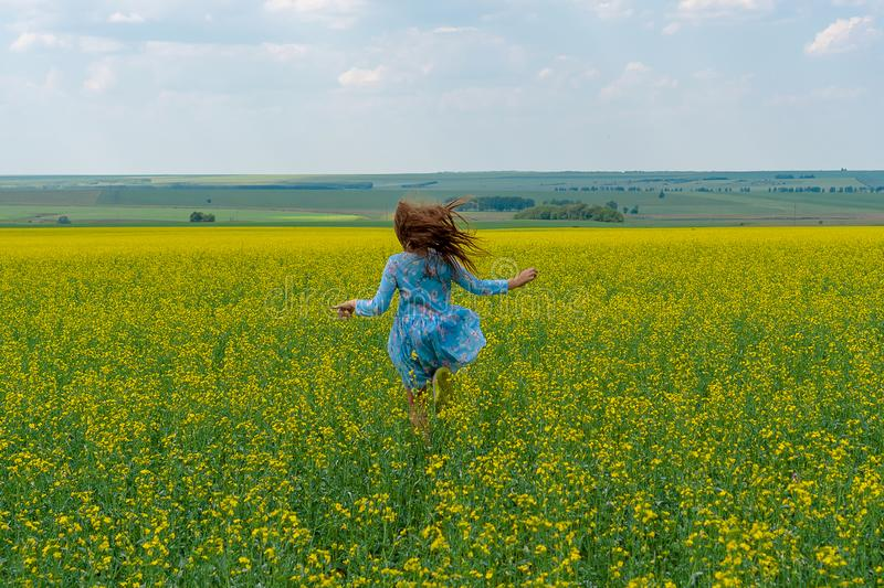 A happy girl with long hair runs across a yellow flower field. Hair develop stock photography