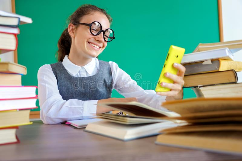 Happy girl looks at the phone and makes a selfie. stock photo