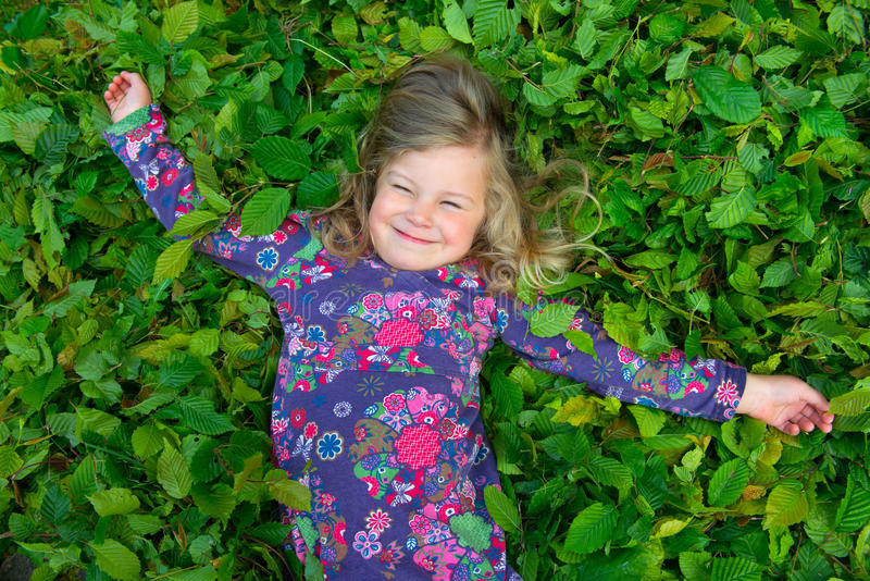 Happy girl is lying in leaves. Happy girl is lying in green leaves stock photos